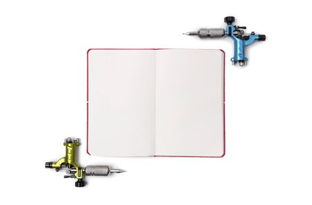 Tattoo machines with open notepad isolated on background. Tattooing artist studio template. Flat lay top view copy space