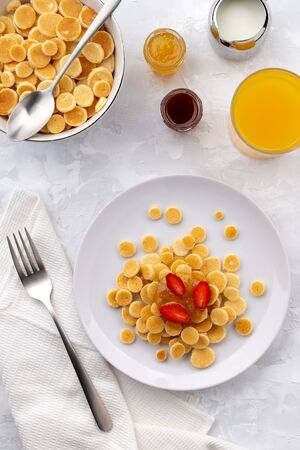 Tiny mini pancake cereal. Home made breakfast with raspberries, jam and juice on gray background. Trendy morning food flat lay top view Фото со стока