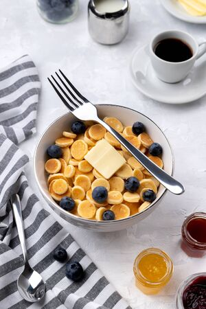 Tiny mini pancake cereal. Home made breakfast with blueberries, jam and coffee on gray background. Trendy morning food