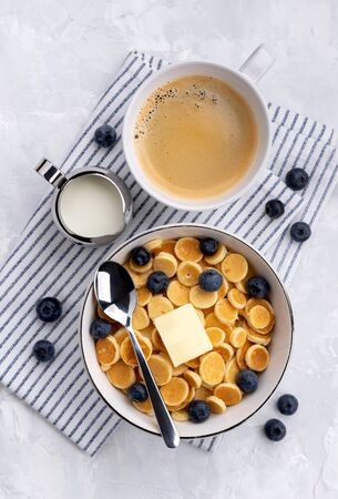 Tiny mini pancake cereal. Home made breakfast with blueberries, jam and juice on gray background. Trendy morning food flat lay top view Фото со стока