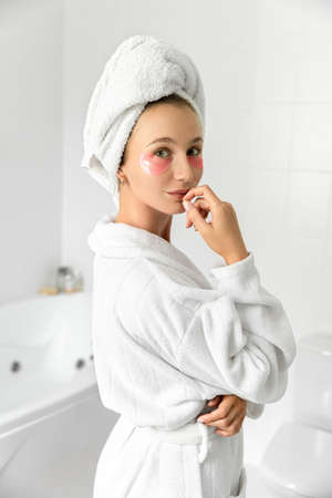 Blonde cute young woman with pink eye patches in white bathroom. Morning wake up self body care at home