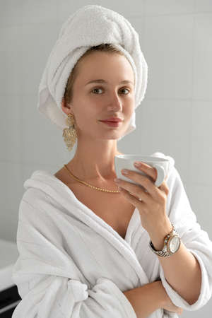 Young woman drink coffee in bathroom. Skin care routine. Slow living stop rushing enjoying life concept