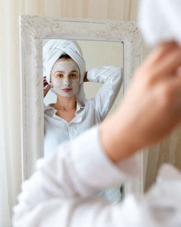 Young beautiful woman apply face mask in bedroom. Mirror reflection. Skin care routine body care concept 免版税图像
