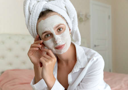 Young beautiful woman apply face mask in bedroom. Skin care routine body care concept 免版税图像