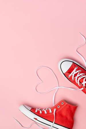 Minimal composition with red sneakers on pink background. Birthday womans day mothers day greeting card.