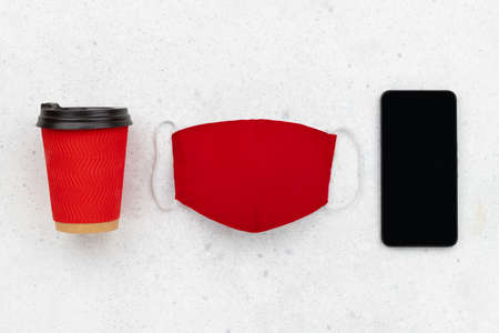 Paper cup with face mask and smartphone on gray background. Flat lay top view new normal autumn winter composition.