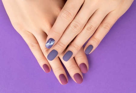 Beautiful purple burgundy matte manicure on creative background. Fashionable spring summer nail design.