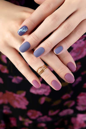 Beautiful womans hand with purple matte manicure on fabric. Fashionable spring summer nail design. 免版税图像