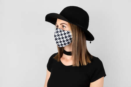 Fashion portrait of beautiful woman in fashionable protective mask. Trendy clothes and accessories. New normal concept