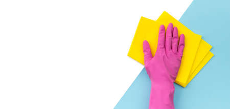 Woman's hand in pink rubber glove wipe by rag blue background. Cleaning service or housekeeping template.