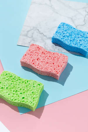 Creative layout with sponges for dishwashing on multicolor background. Cleaning service concept