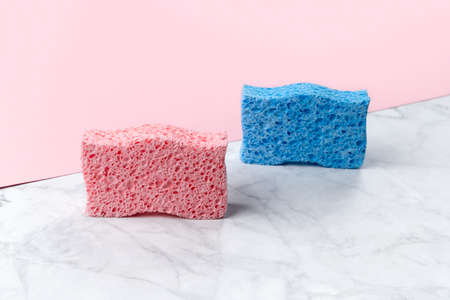 Creative layout with sponges for dishwashing on pink and marble double background. Cleaning service template