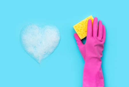 Woman's hand in pink rubber glove wash by sponge blue background. Cleaning service or housekeeping creative layout.