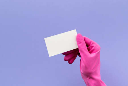 Woman's hand in pink rubber glove holding business card on purple background. Cleaning service or housekeeping mock up.