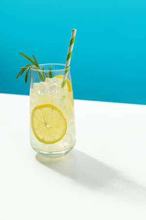Glass ice lemonade with rosemary on blue background. Minimal style composition summer drink restaurant template.