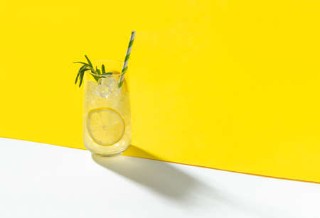 Glass ice lemonade with rosemary on yellow background. Minimal style composition summer drink restaurant template.