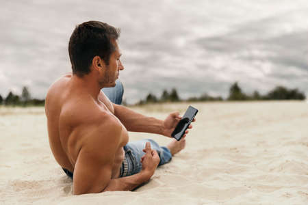 Pensive handsome young man with smartphone in desert. Fashion model in trendy casual clothes posing outdoors.