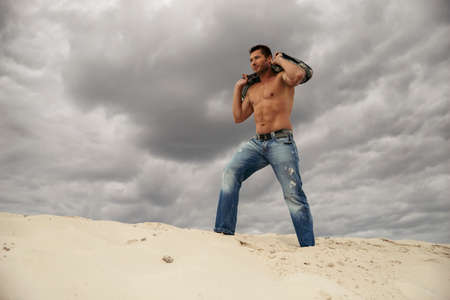 Muscular young man with sand bag in desert. Fitness training workout concept. 免版税图像
