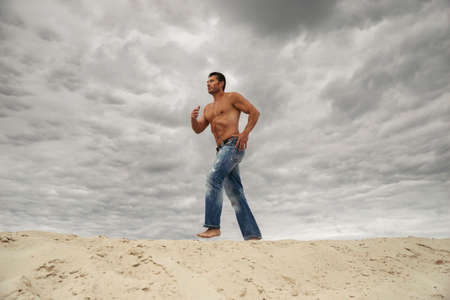 Muscular young man running over sand dunes. Fitness training concept workout in desert. 免版税图像