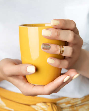 Woman's hands with yellow shiny nail design holding cup. Fashionable trendy female manicure in minimal style. Beauty salon template