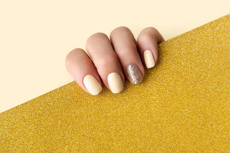 Manicured woman's hands with trendy yellow manicure in minimal style. Fashionable summer spring nail design. 免版税图像 - 155092034