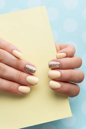 Manicured woman's hands with trendy yellow manicure in minimal style. Fashionable summer spring nail design.
