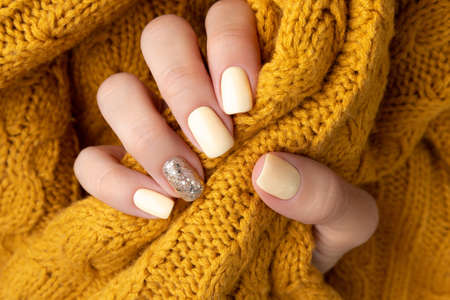 Manicured woman's hands with warm wool yellow sweater. Fashionable autumn winter nail design. 免版税图像