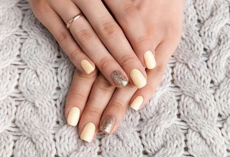 Manicured woman's hands with warm wool beige sweater. Fashionable autumn winter nail design.