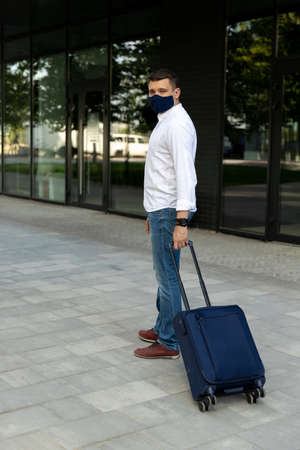 Man in casual clothes walking with a suitcase. Young traveler in protective cloth face mask new social behavior new normal concept