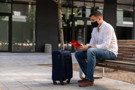 Man in casual clothes sitting on a bench with a suitcase. Young traveler in protective cloth face mask new social behavior new normal concept Standard-Bild