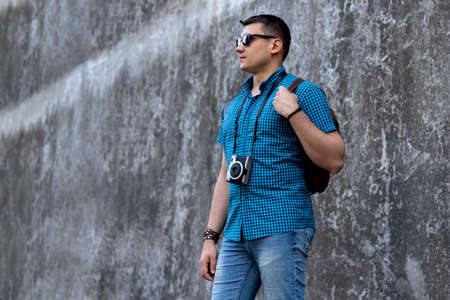 Man in casual clothes walking through the city with camera and backpack. Travel vacation concept
