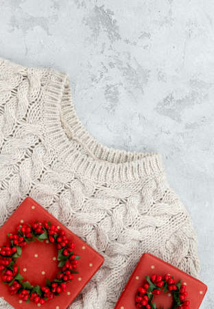 Christmas fashion sale mockup template with sweater and gifts on concrete background.