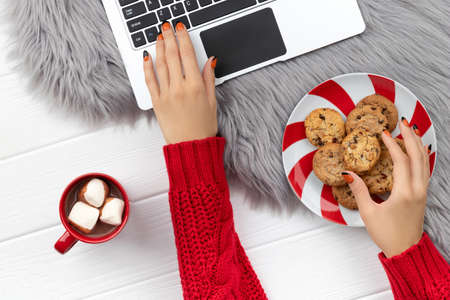 Womans hands typing on the keyboard with cocoa and cookies on furry background. Christmas online shopping working from home concept. 免版税图像