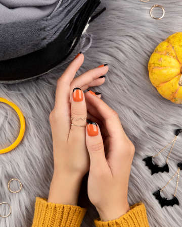 Manicured womans hand with f?shion accessories over furry background. Trendy autumn halloween orange nail design.