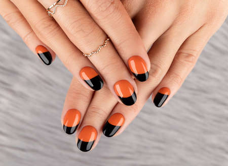 Manicured woman's hand over furry background. Trendy autumn halloween orange nail design.