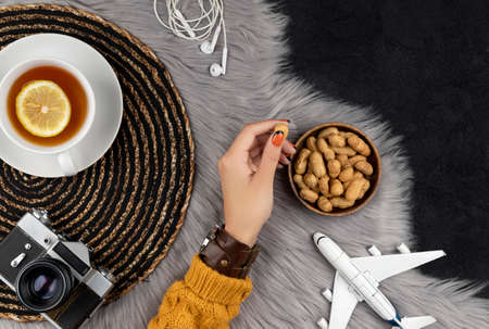 Womans hand in sweater with old instant camera plane and tea. Autumn vacation travel concept top view flat lay