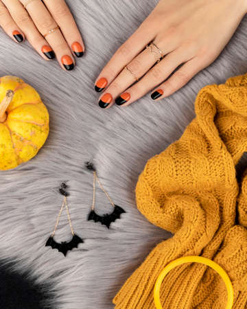 Manicured womans hand with f shion accessories over furry background. Trendy autumn halloween orange nail design. 免版税图像
