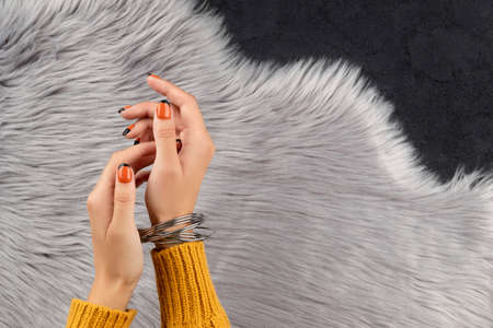 Manicured womans hand over furry background. Trendy autumn halloween orange nail design.