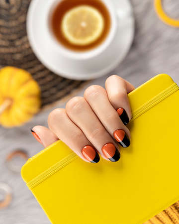 Manicured woman's hand holding yellow notepad on gray background. Trendy autumn halloween orange nail design. 免版税图像