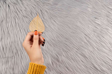 Manicured woman's hand holding yellow leaf on gray fluffy background. Trendy autumn halloween orange nail design.