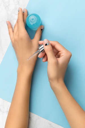 Groomed womans hands with nail design holding bottle of serum