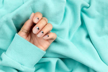 Beautiful groomed womans hand with nude and blue matte nail design 免版税图像
