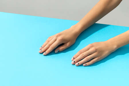 Womans hands with nude nail design over blue background 免版税图像 - 155790093