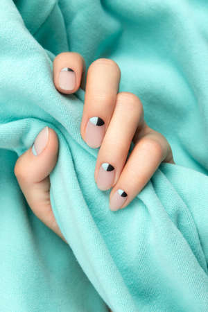 Beautiful groomed womans hands with nude and blue matte nail design