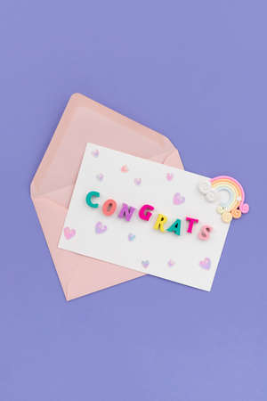 Open pink envelope with the word congrats on violet background