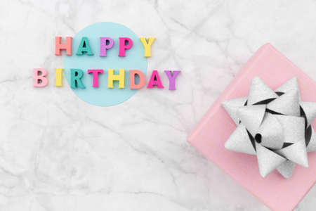 Happy birthday text from wooden colorful letters with gift box