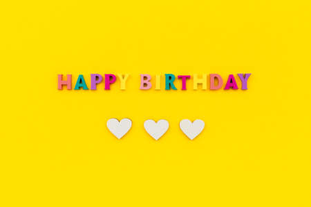 Happy birthday text from wooden colorful letters with hearts