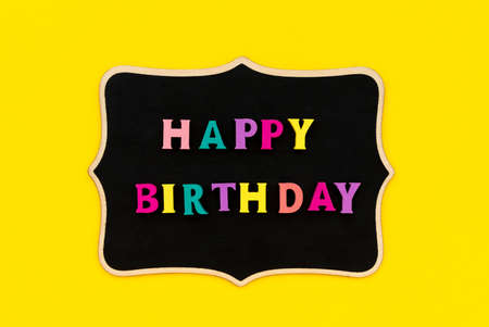 Happy birthday inscription from colorful letters on wooden board