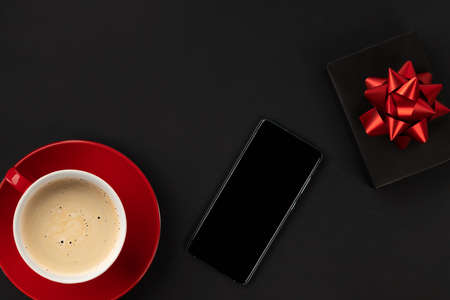 Creative flat lay top view composition smartphone, coffee cup and gift. Black friday thanksgiving christmas template shopping sale mockup