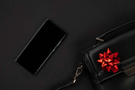 Creative flat lay top view composition with bag, smartphone and bow